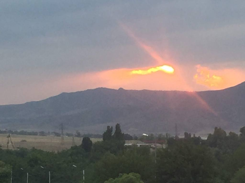 Sun setting against clouds, above a hill.